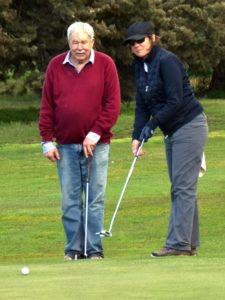 Louise receives some putting advice from Bill during the President's Day Ambrose event